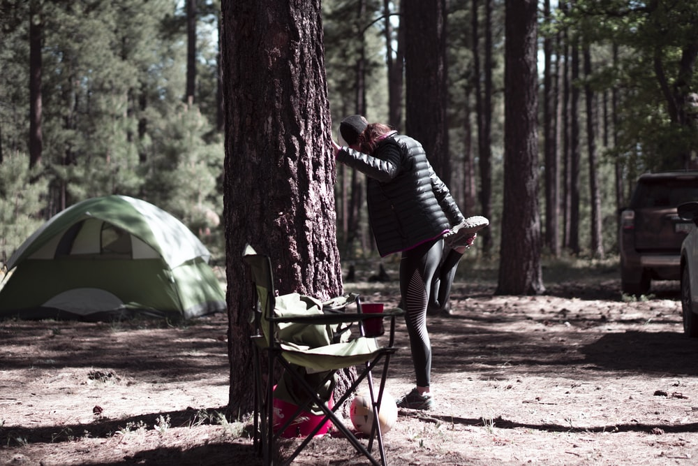 man in black and white striped long sleeve shirt and black pants standing near tent
