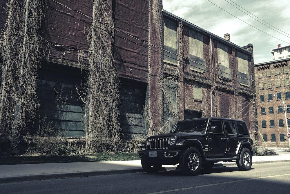 black jeep wrangler parked beside brown brick building