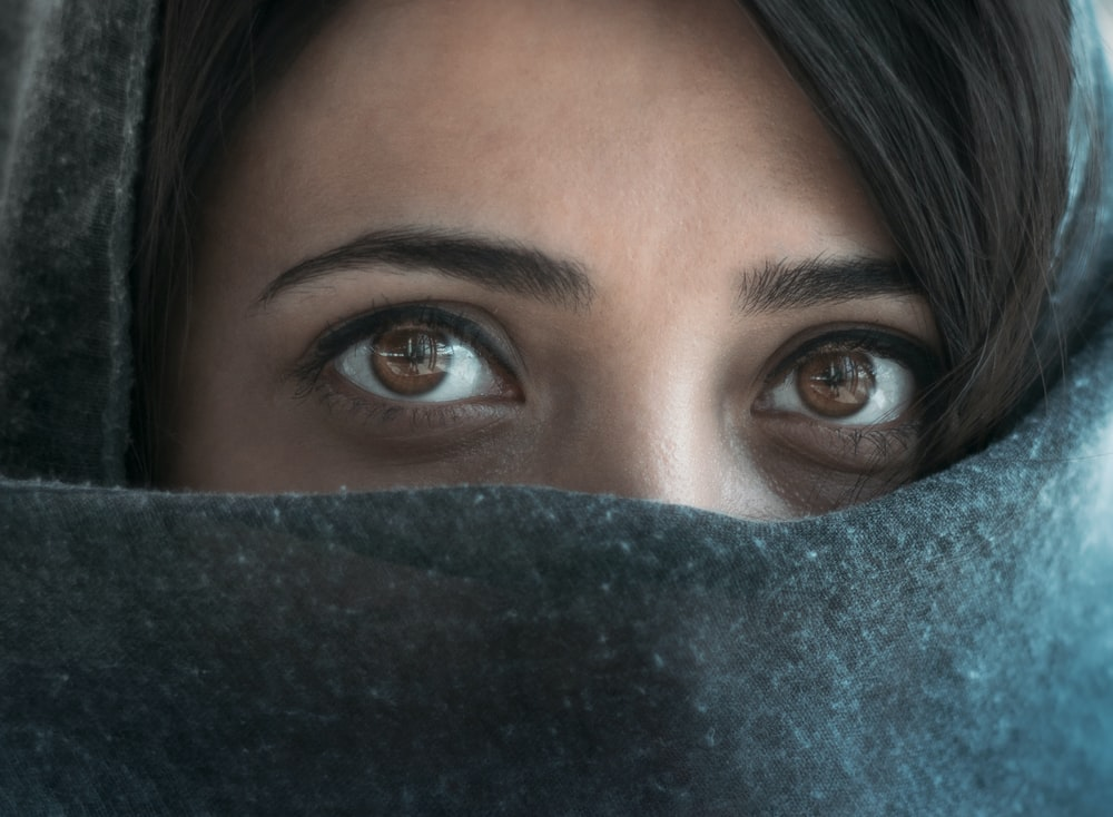 woman with blue eyes covering her face with blue textile