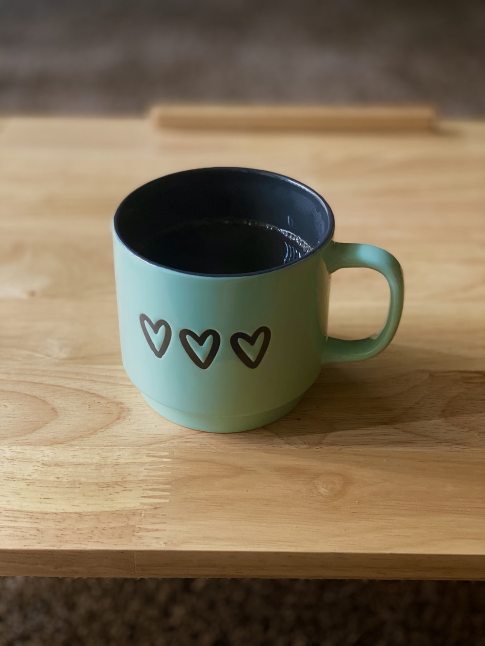 white and green ceramic mug on brown wooden table