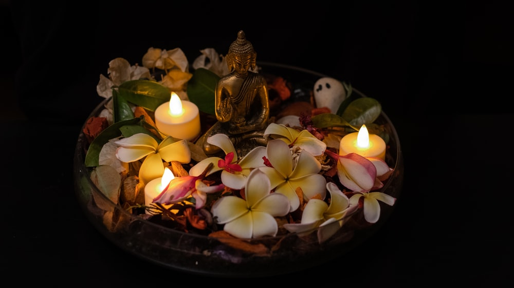 gold buddha figurine on brown round tray