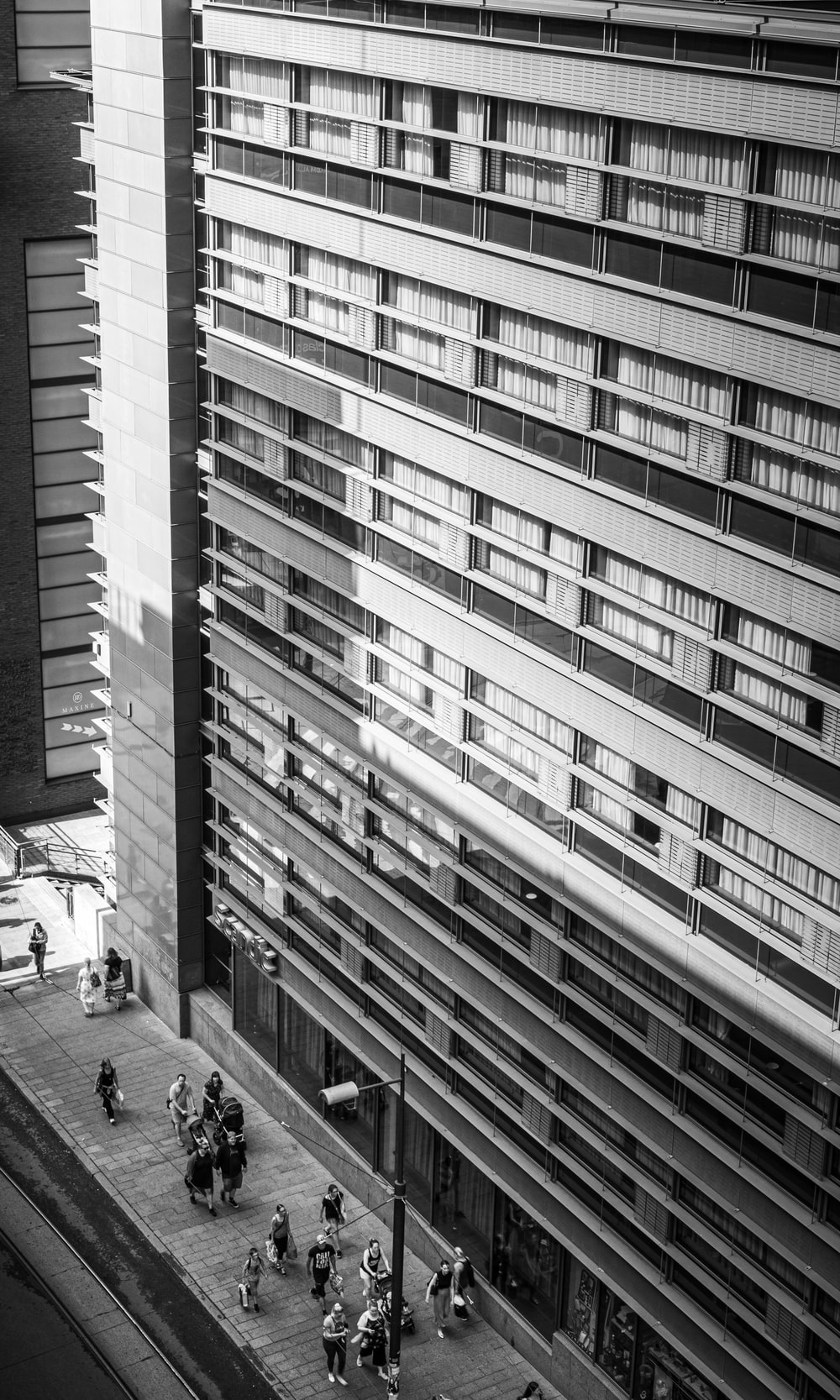 grayscale photo of people walking on street in between high rise buildings