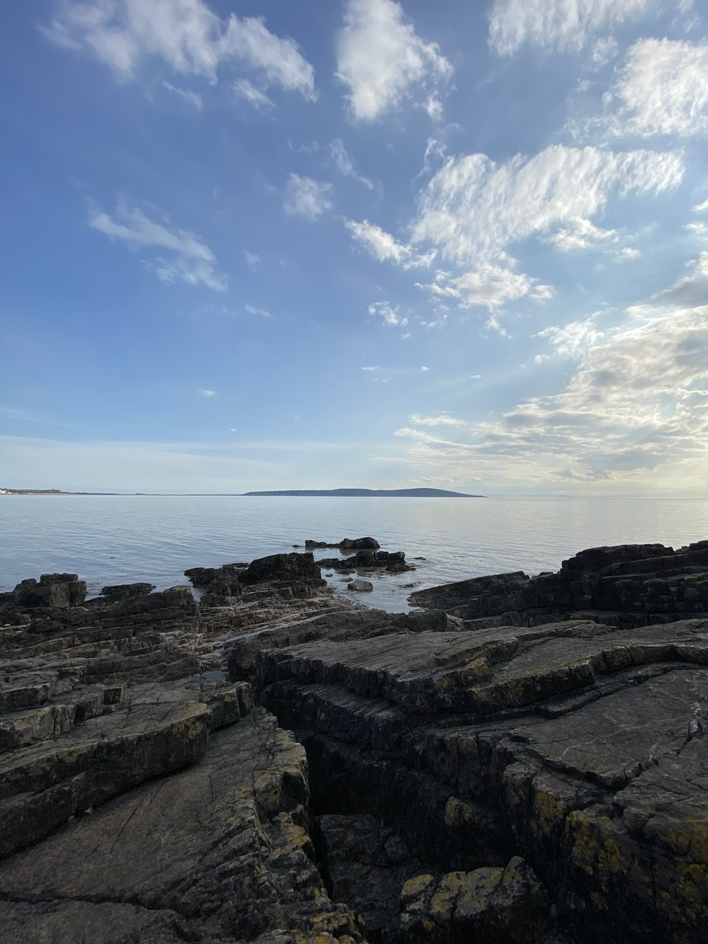 brown rocky shore under blue sky during daytime