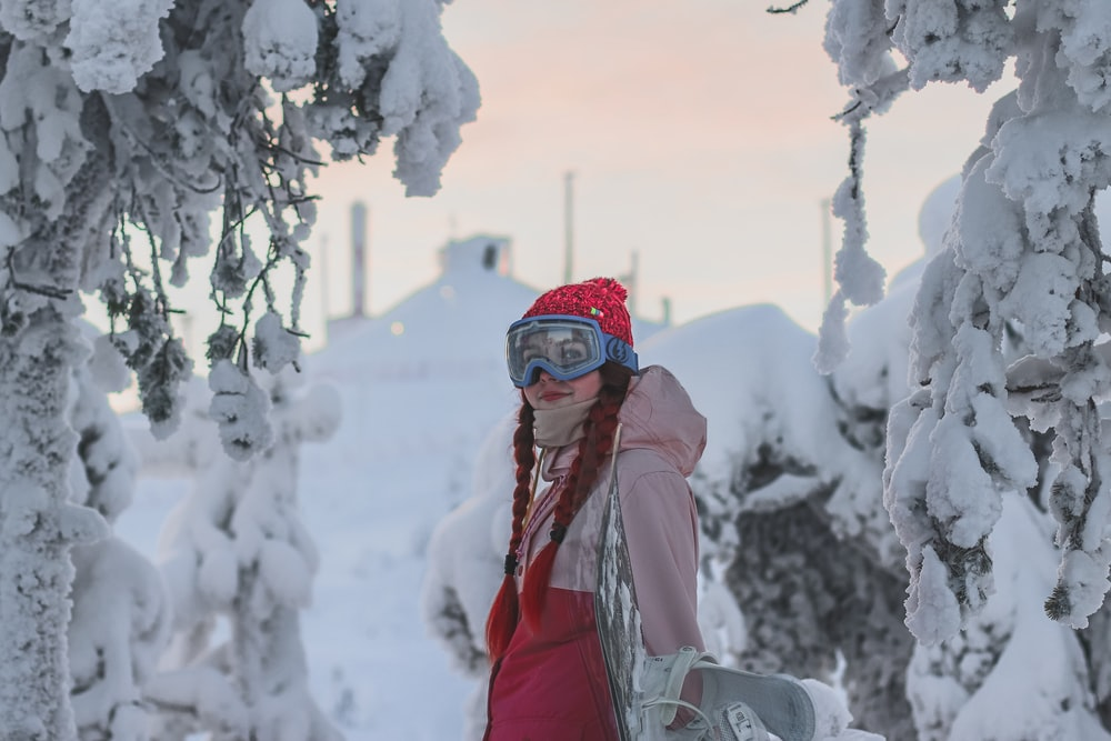 woman in red jacket and red knit cap standing on snow covered ground during daytime