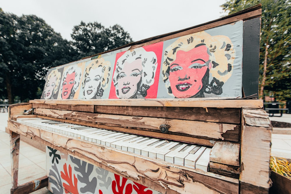 white and red graffiti on brown wooden fence