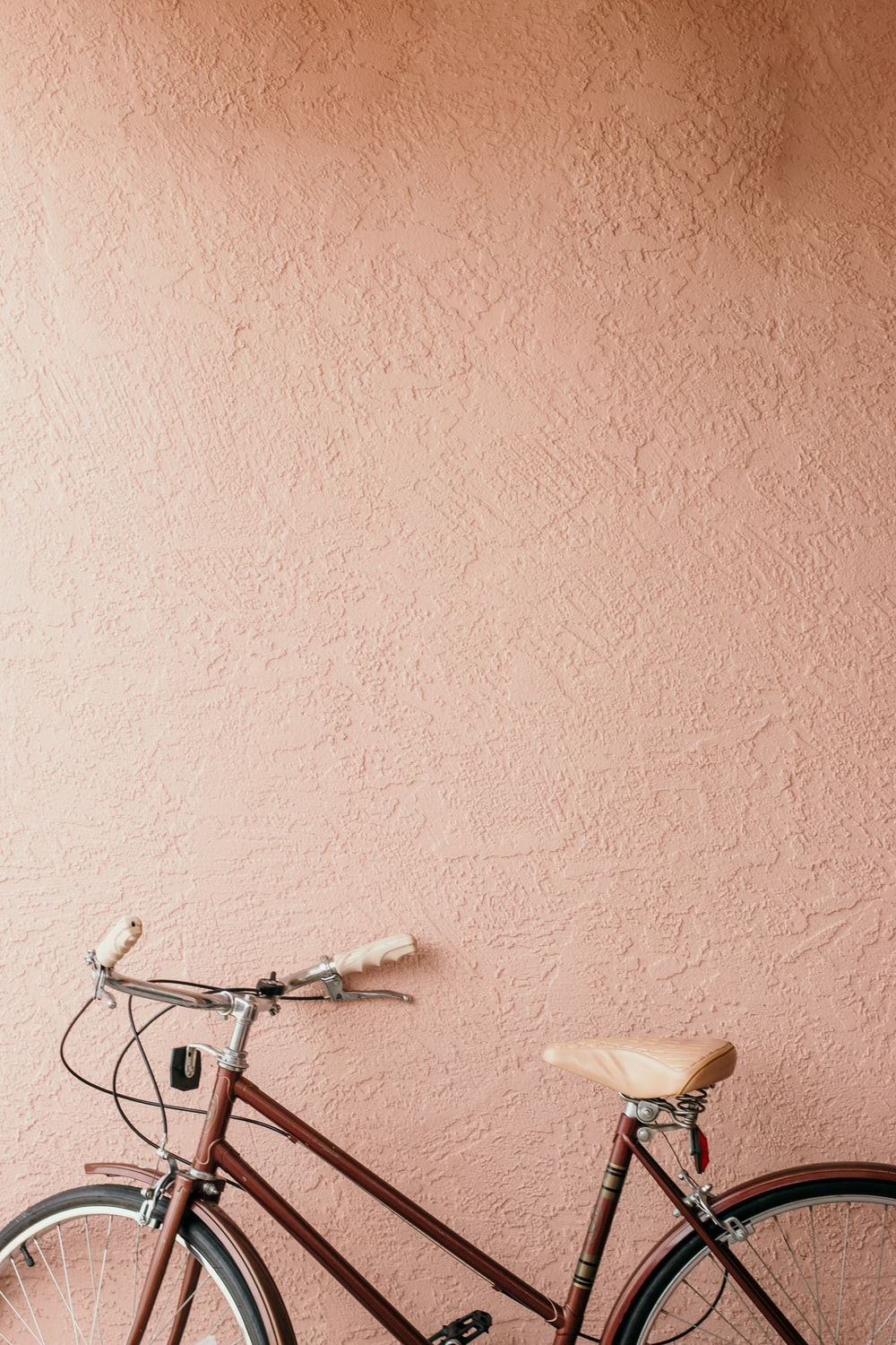 white city bike beside pink wall