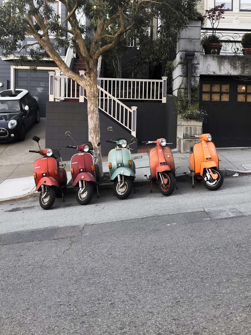 red and green motor scooter parked beside road during daytime