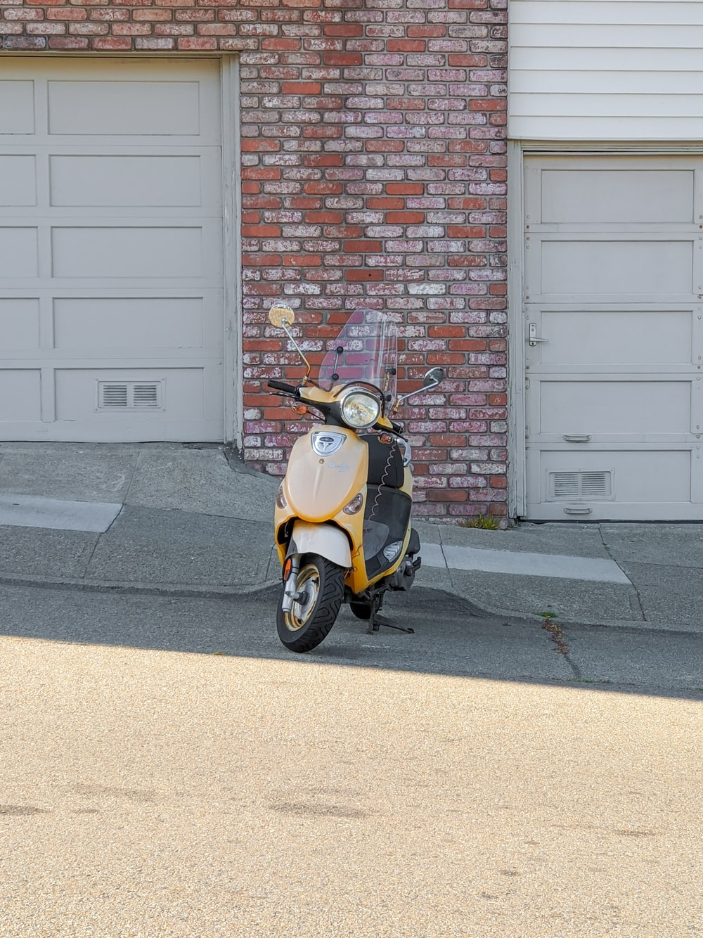 yellow and black motor scooter parked beside brown brick wall
