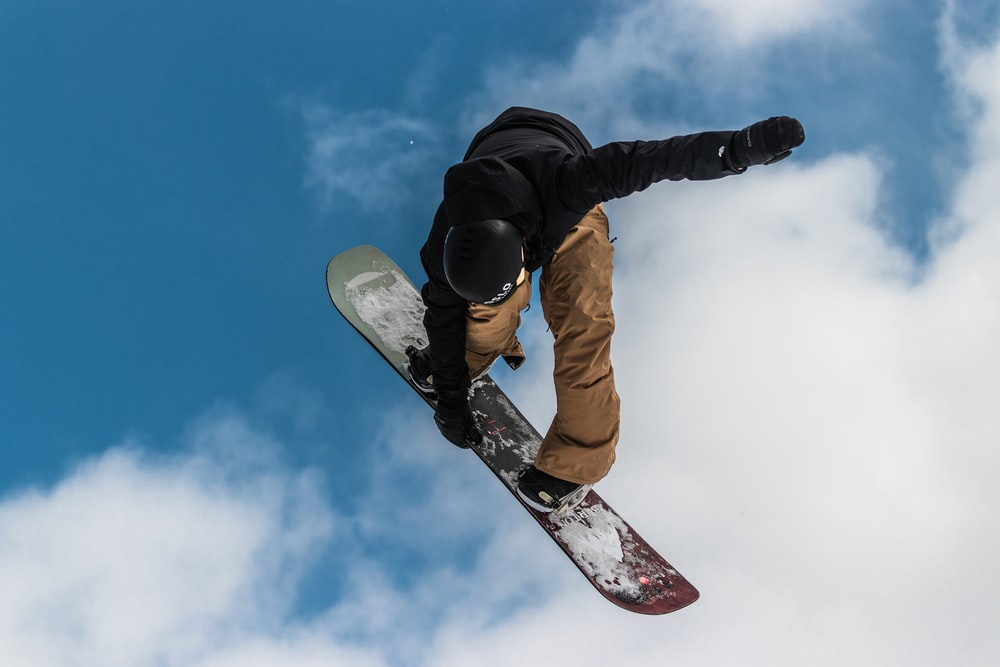 man in black jacket and brown pants riding white and red snowboard