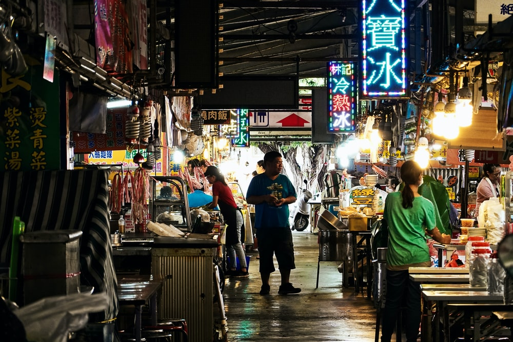 people standing in front of food stall during nighttime