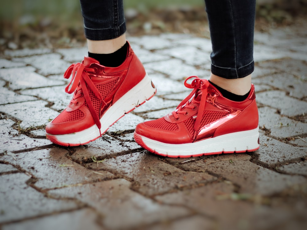 person in red nike sneakers
