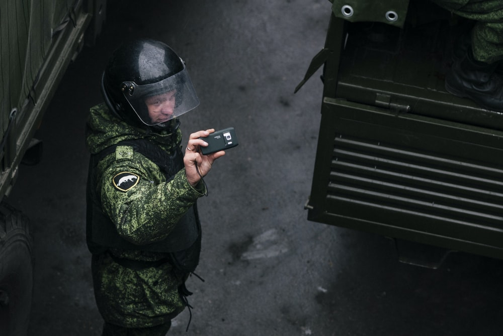 man in green and black camouflage jacket holding black smartphone