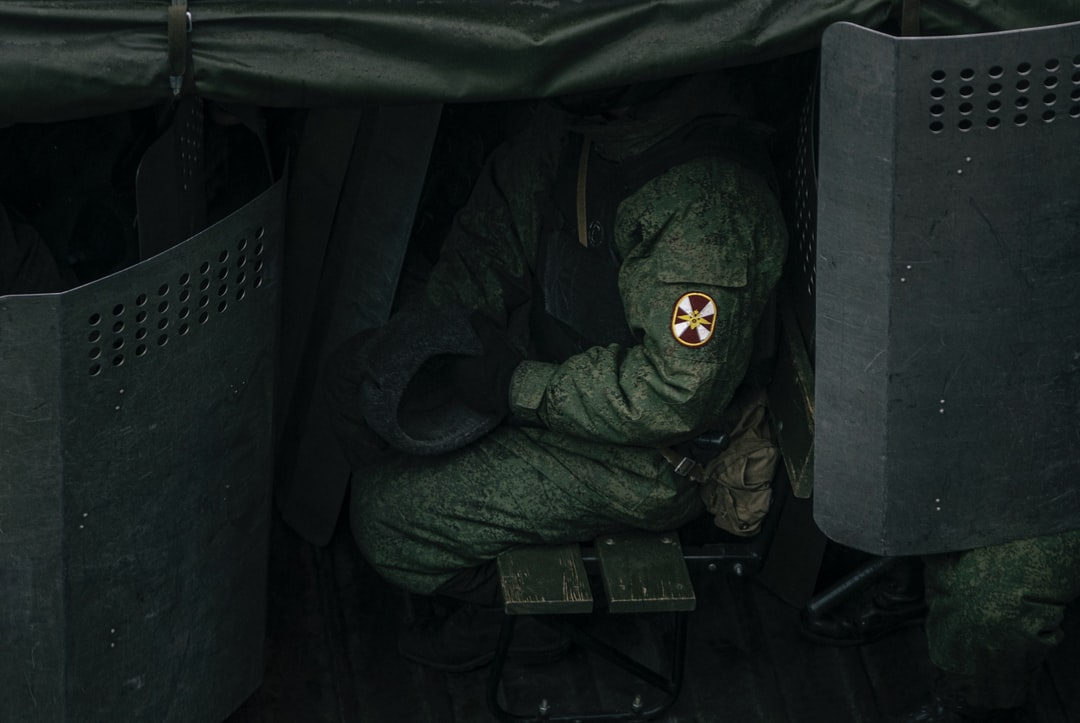 A military man in equipment in the back of a military truck.
