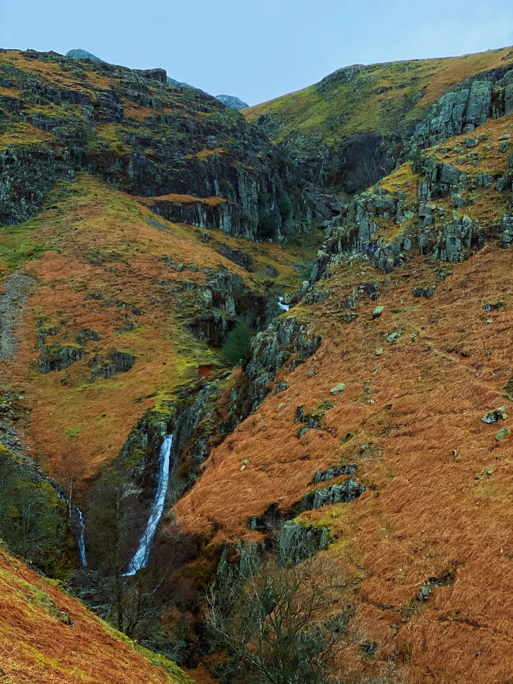 waterfalls in the middle of brown and green mountains