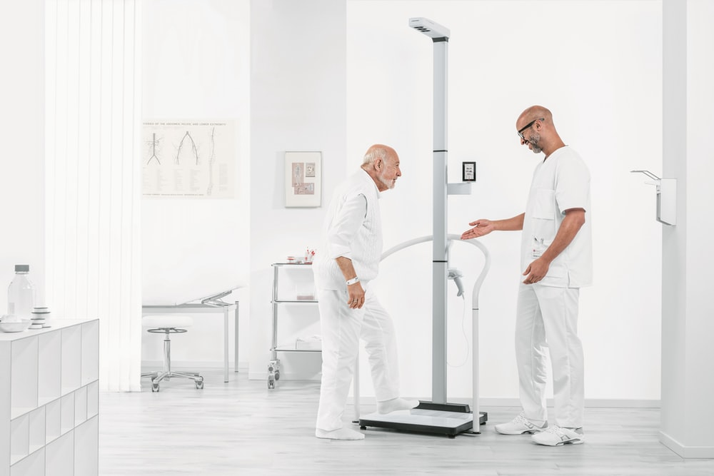 man in white t-shirt and white pants standing on black exercise equipment