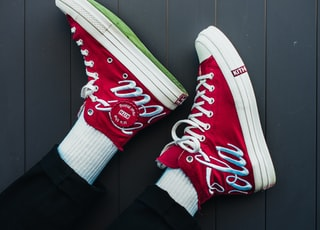 person wearing red and white converse all star high tops