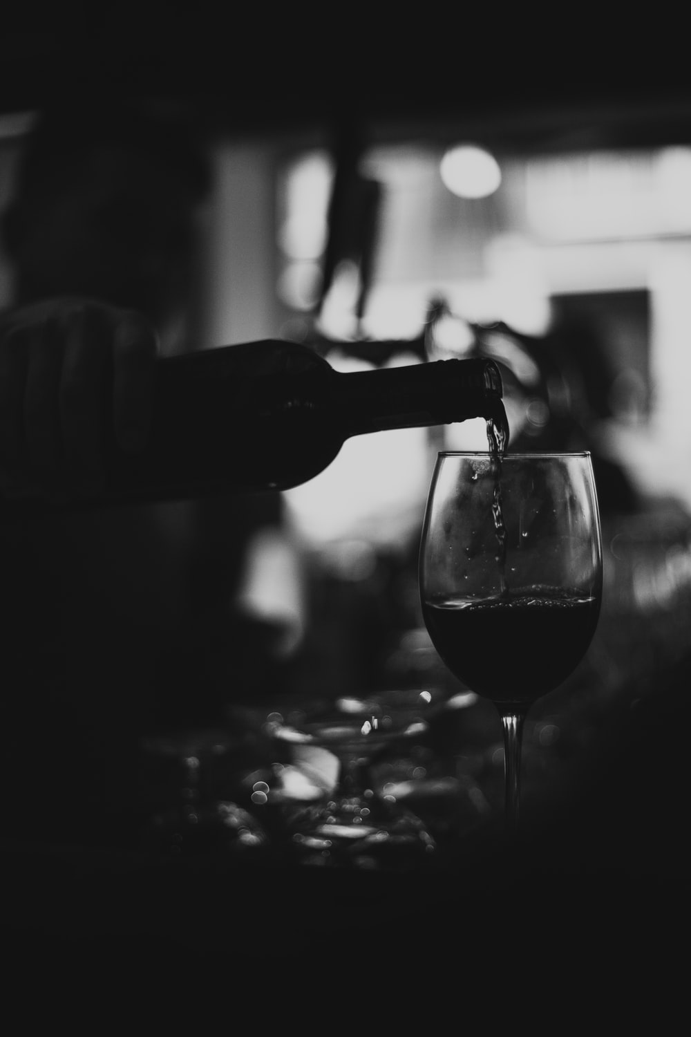 grayscale photo of person pouring wine on clear wine glass