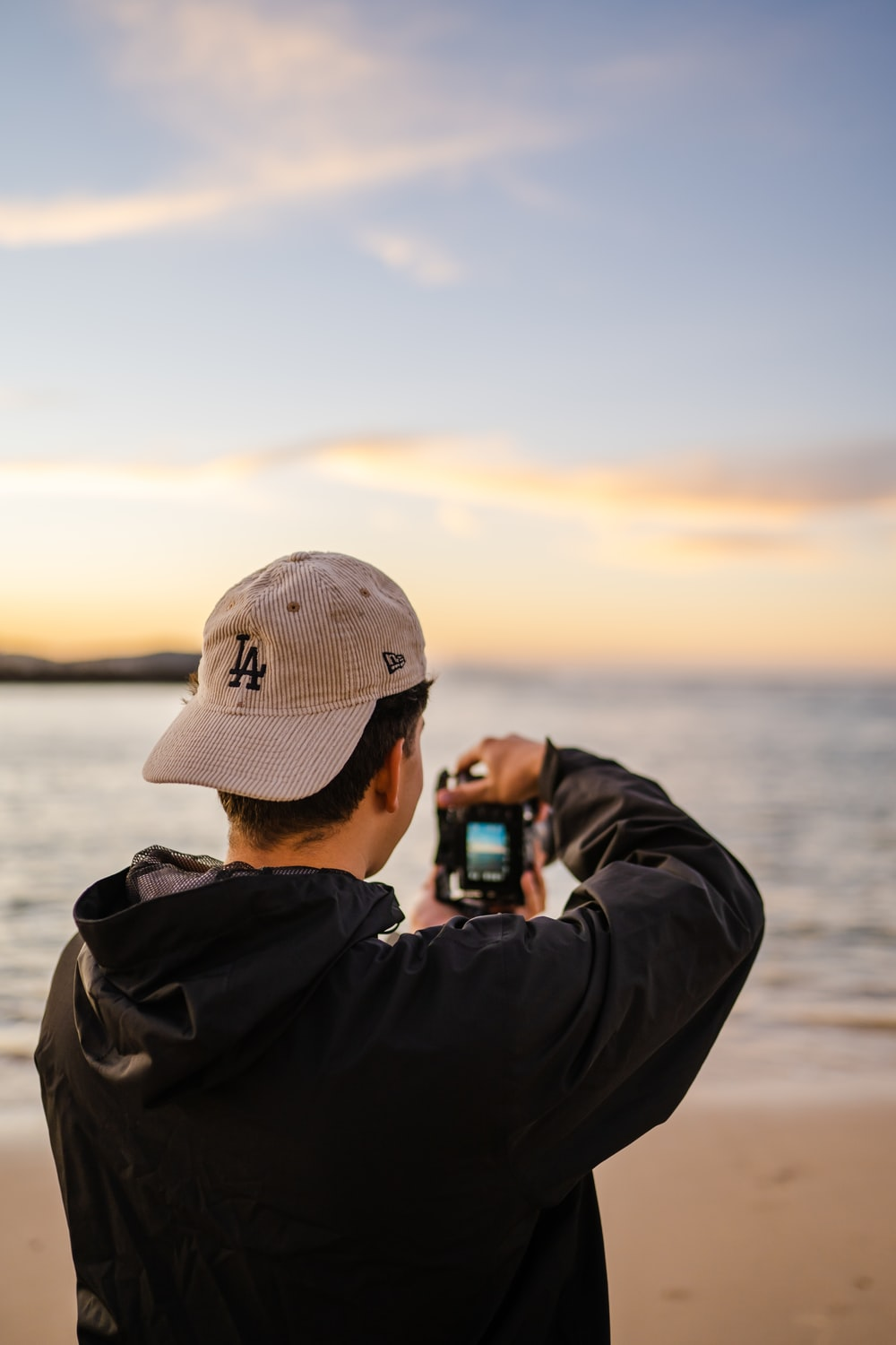 man in gray jacket and gray cap taking photo of sea during daytime
