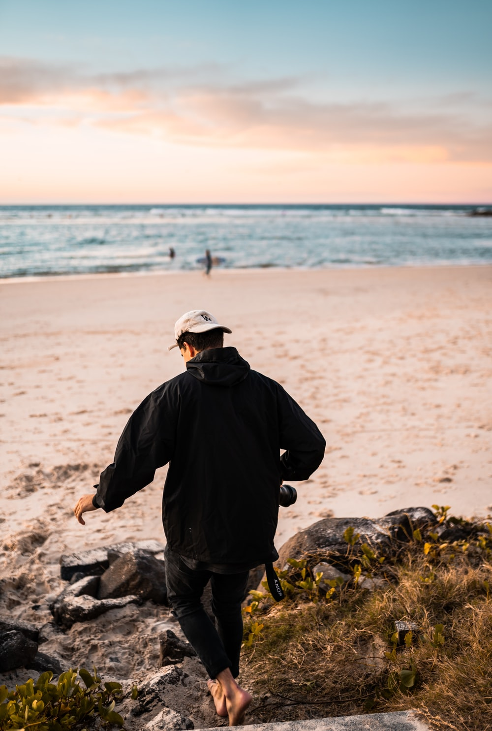 man in black jacket and gray cap standing on gray rock near sea during daytime