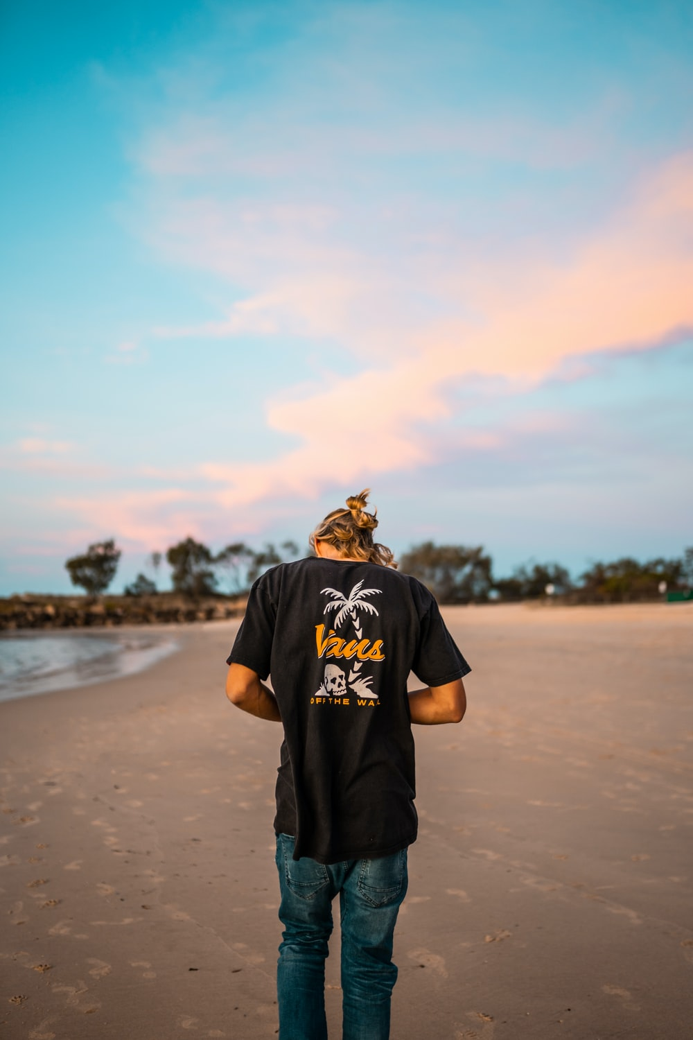 man in black crew neck t-shirt standing on brown sand during daytime