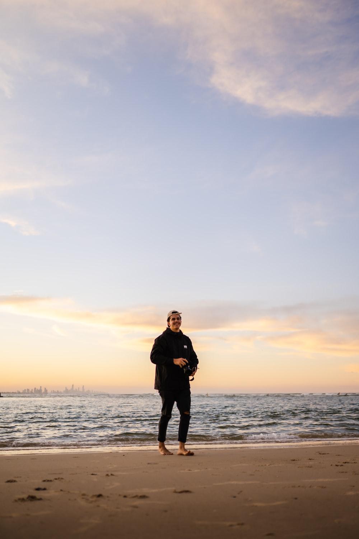man in black jacket standing on seashore during sunset