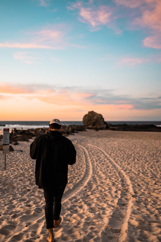 man in black jacket standing on sand during daytime