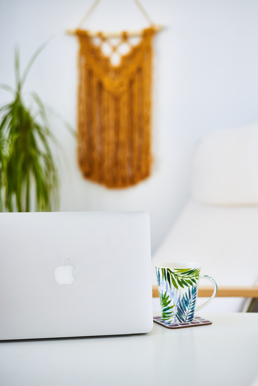 macbook air on white and yellow floral ceramic mug