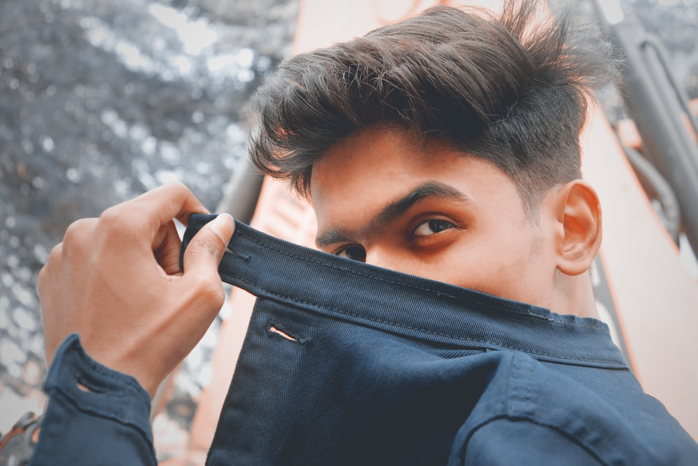 person holding black leather bag