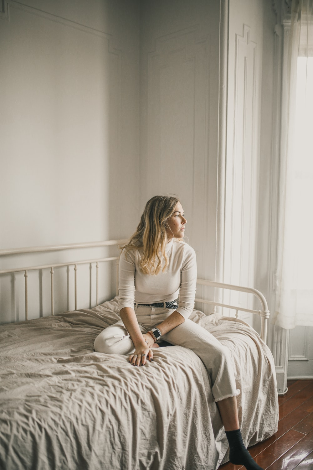 woman in white long sleeve shirt sitting on bed