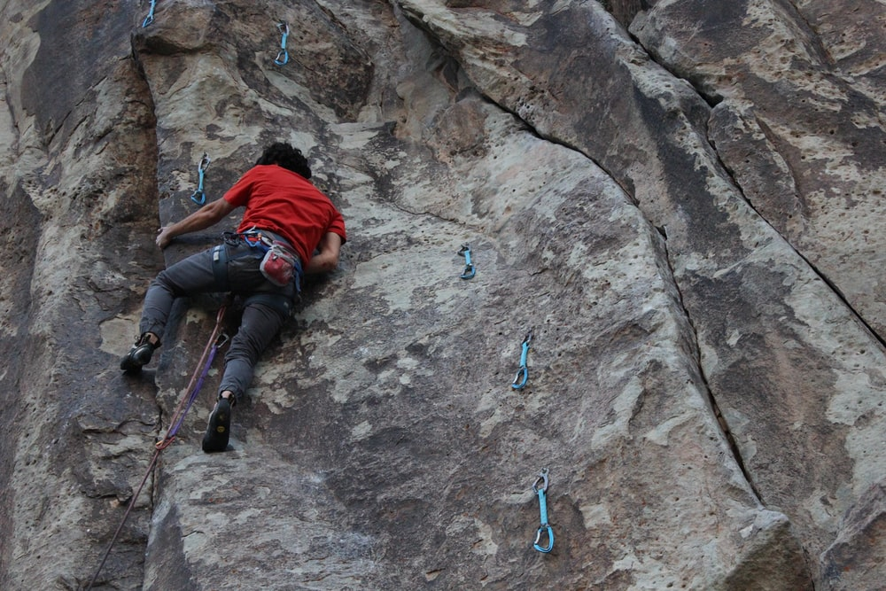 man in red jacket climbing on rocky mountain during daytime