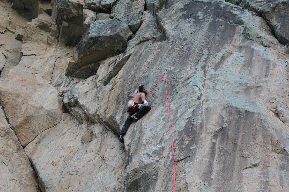 man climbing on rocky mountain during daytime