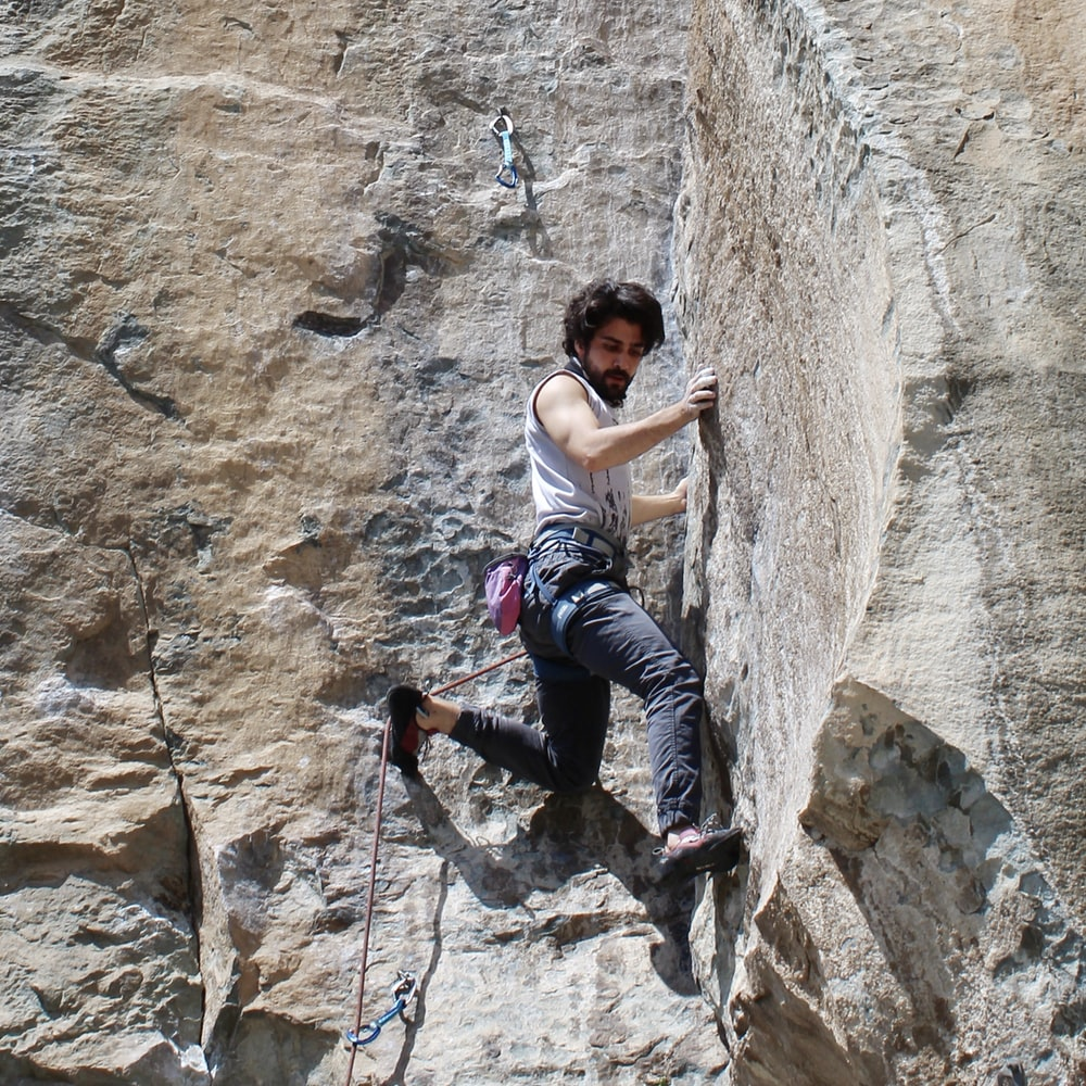 woman in white tank top and blue denim jeans climbing on brown rock during daytime