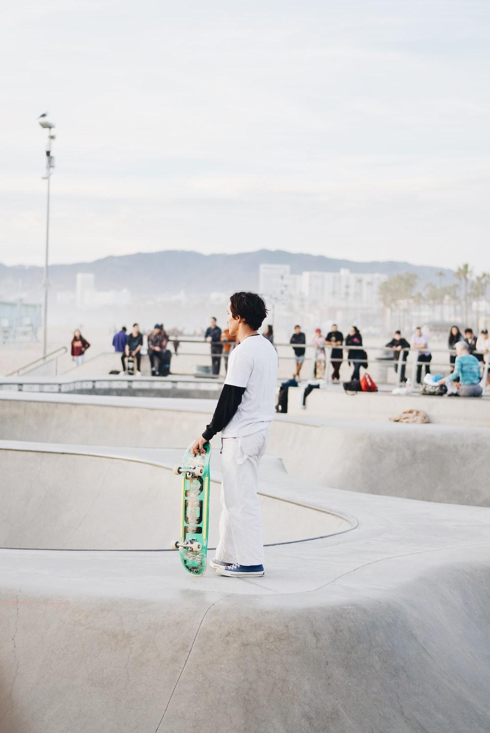 man in white dress shirt and green pants sitting on green skateboard during daytime