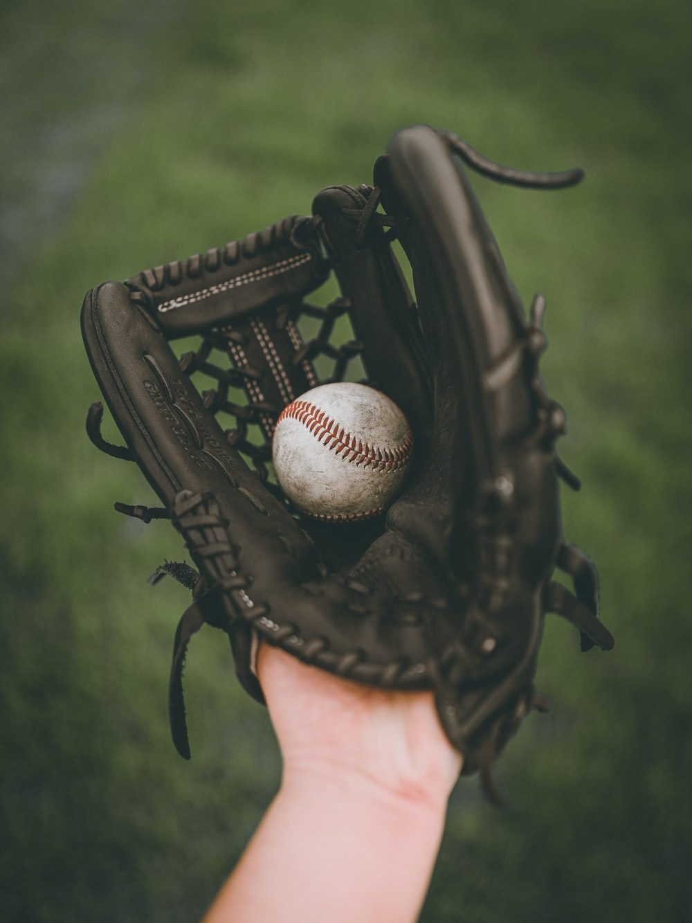 person holding baseball ball in black leather baseball mitt
