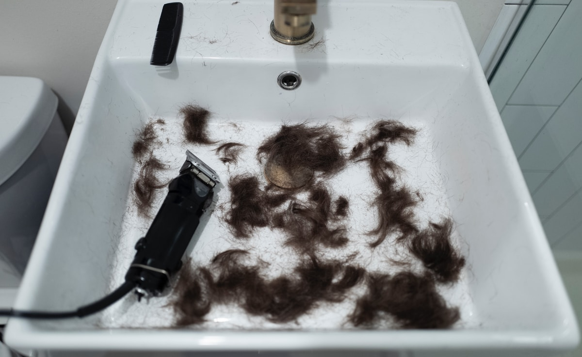 White basin with clippers and several tufts of dark brown hair