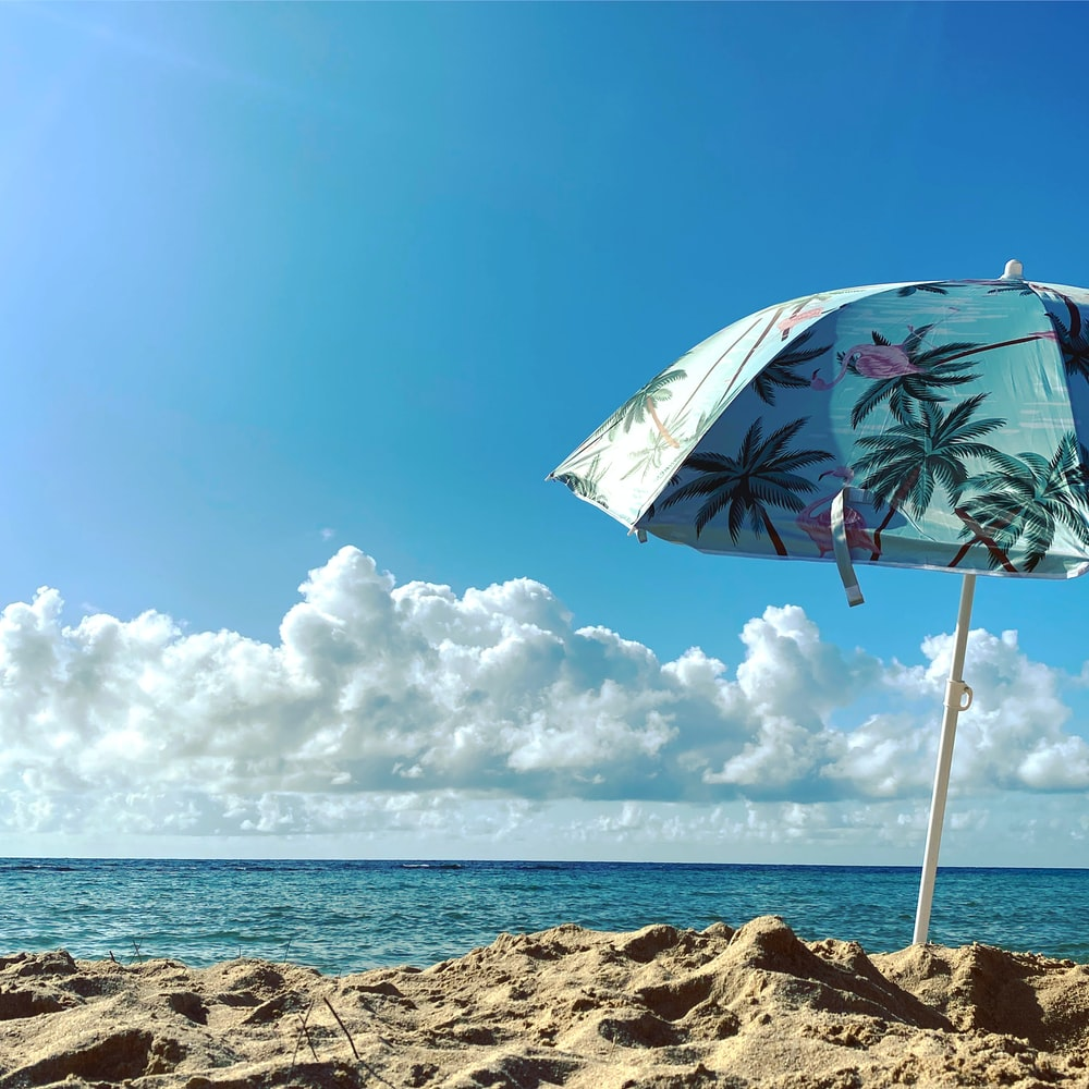 white and green umbrella on beach shore during daytime