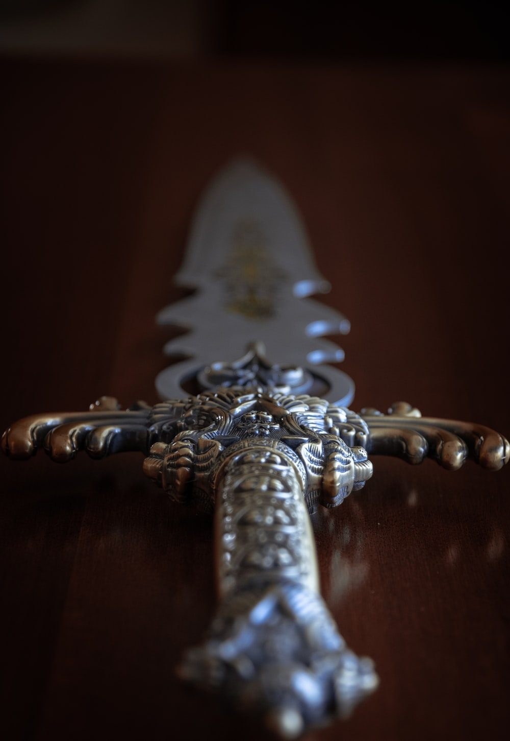 silver sword on brown wooden table