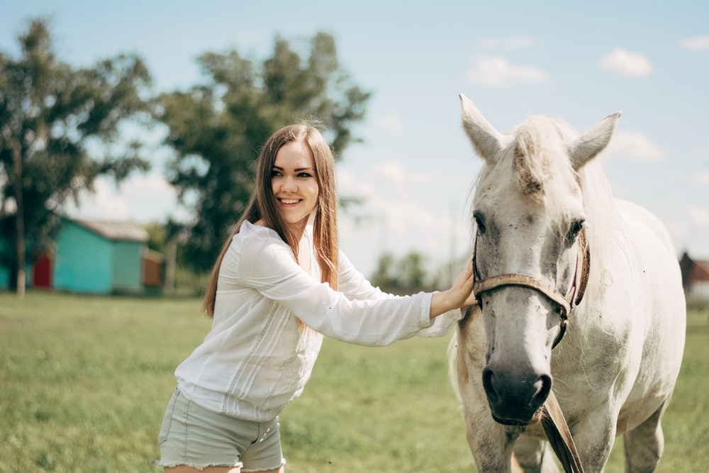 woman in white long sleeve shirt riding white horse during daytime