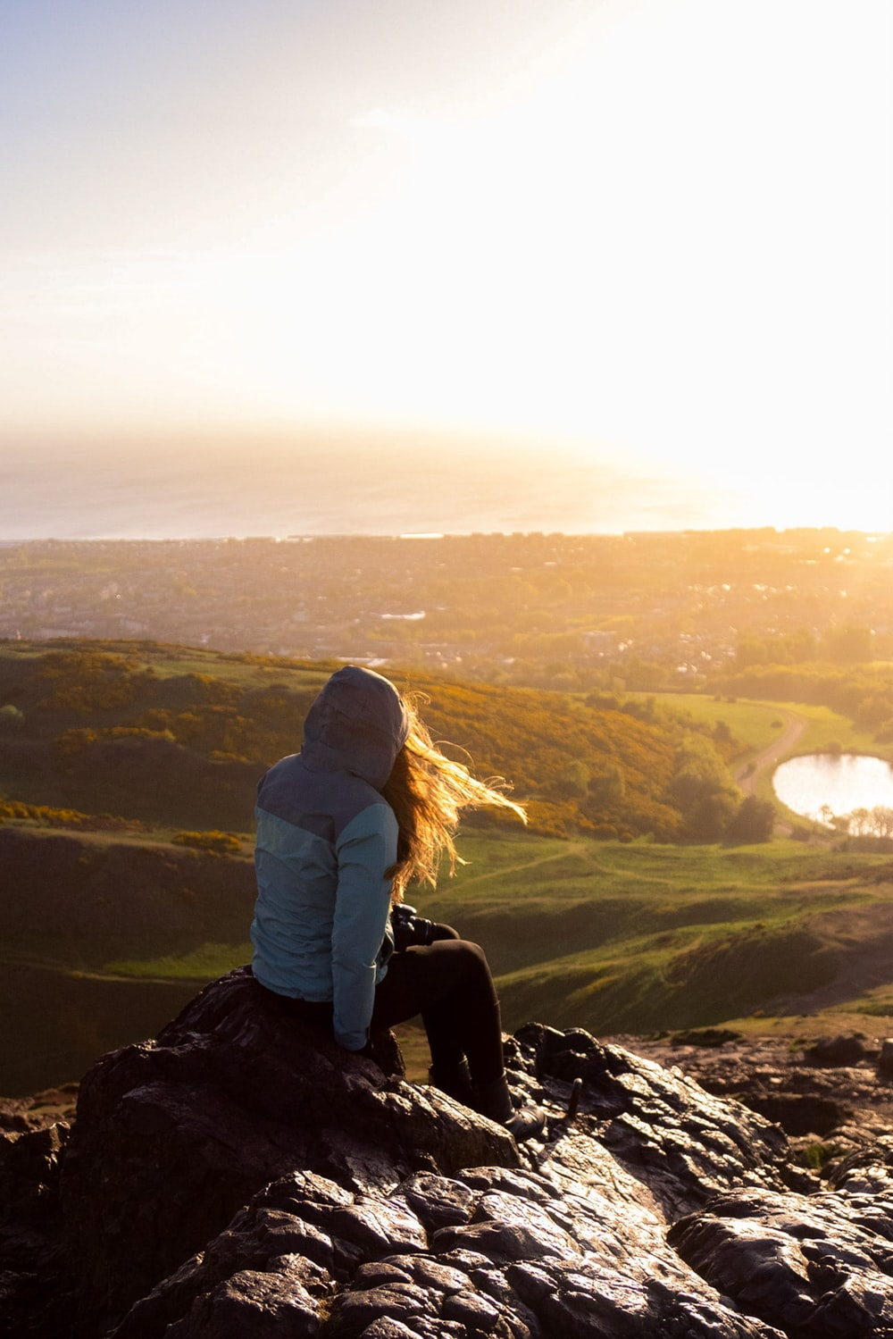 woman in gray hoodie sitting on rock during daytime