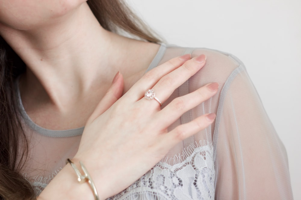woman in white lace top wearing gold ring