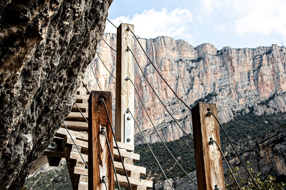 brown wooden ladder on brown rock formation during daytime
