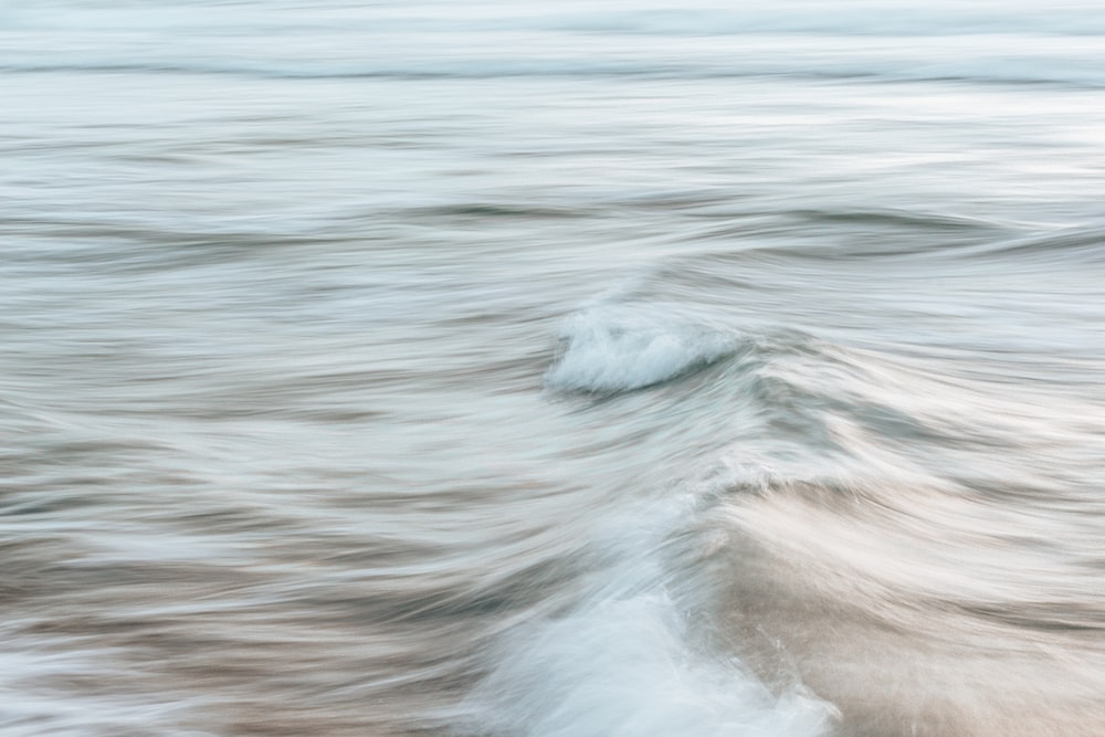 water waves hitting brown sand