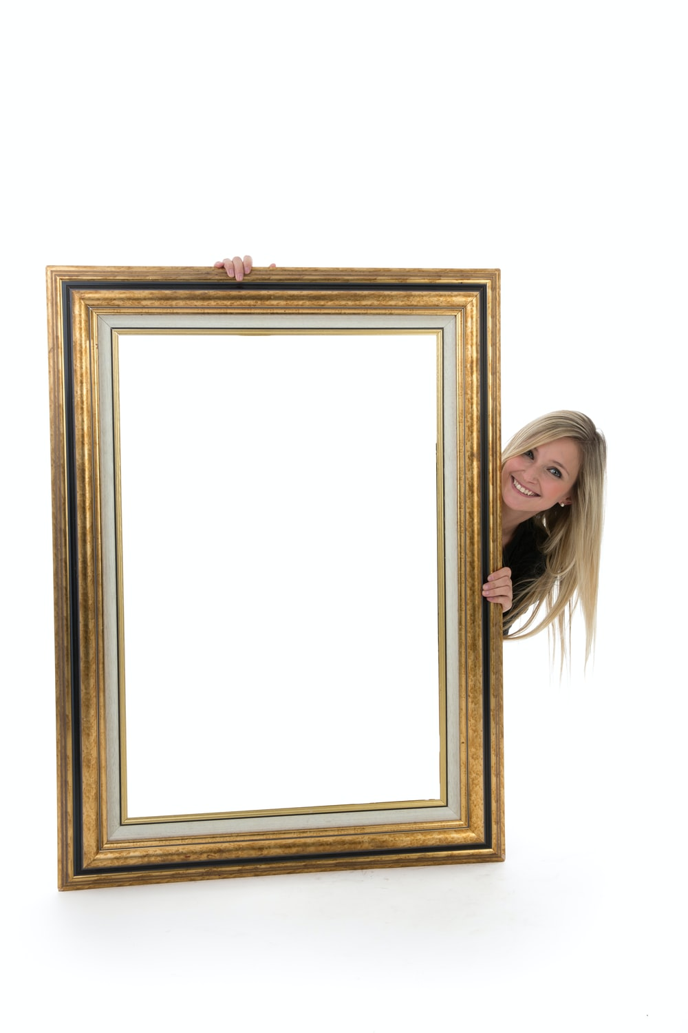 woman in black shirt standing beside brown wooden frame