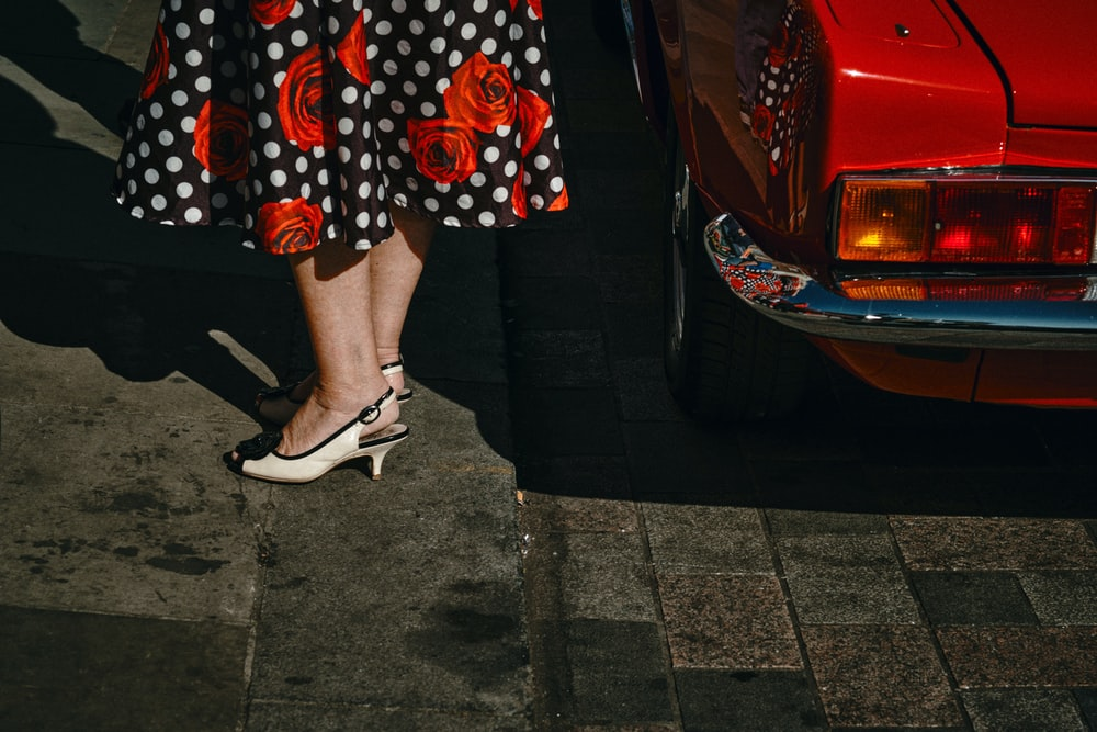 woman in black white and red polka dot skirt and white leather peep toe heeled shoes