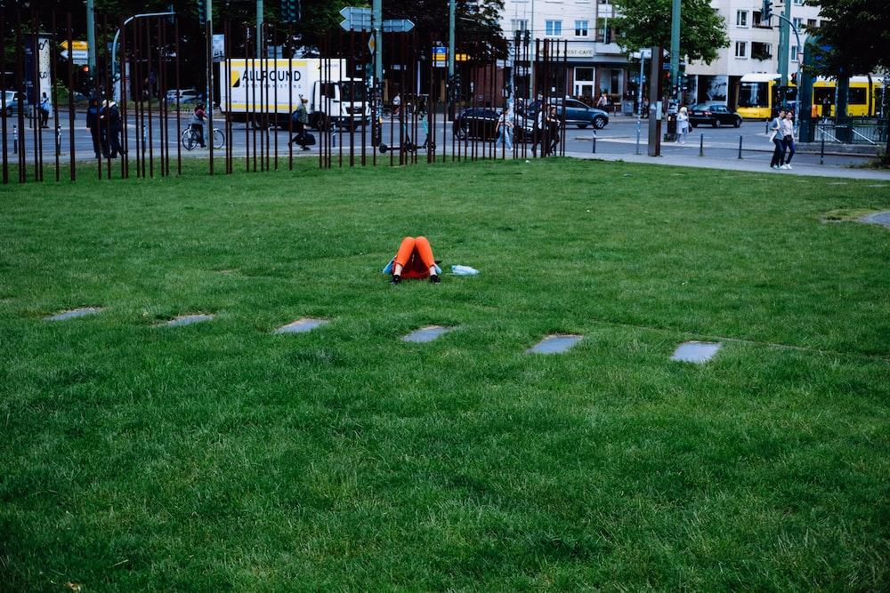 person in orange hoodie sitting on green grass field during daytime