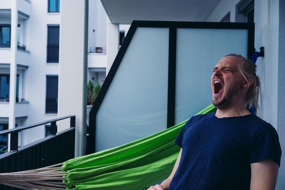 man in blue crew neck shirt standing beside green hammock