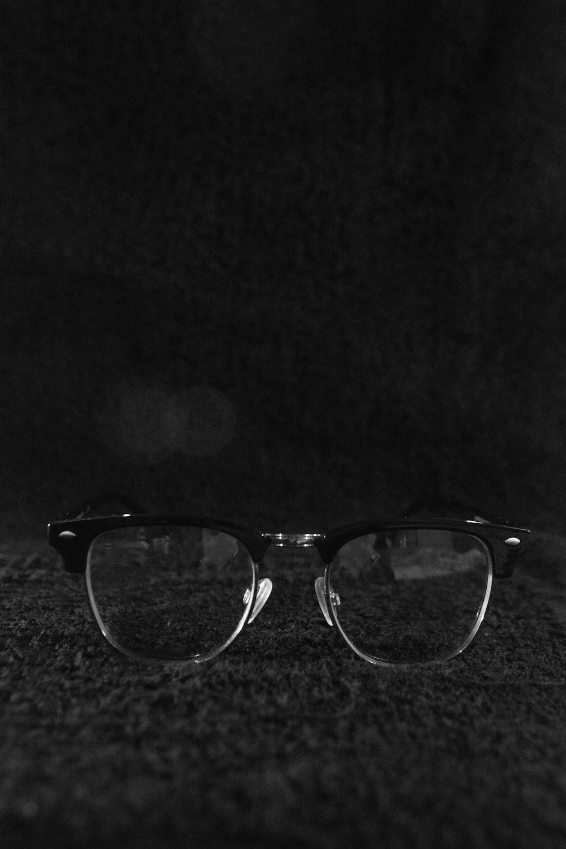 black framed eyeglasses on black textile