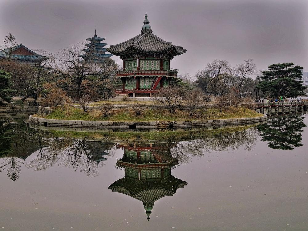 green and brown pagoda temple near lake