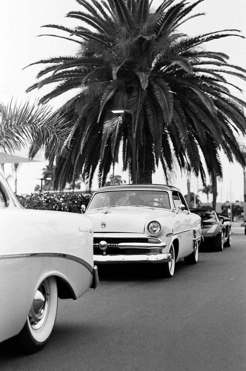 grayscale photo of classic car parked on the side of the road