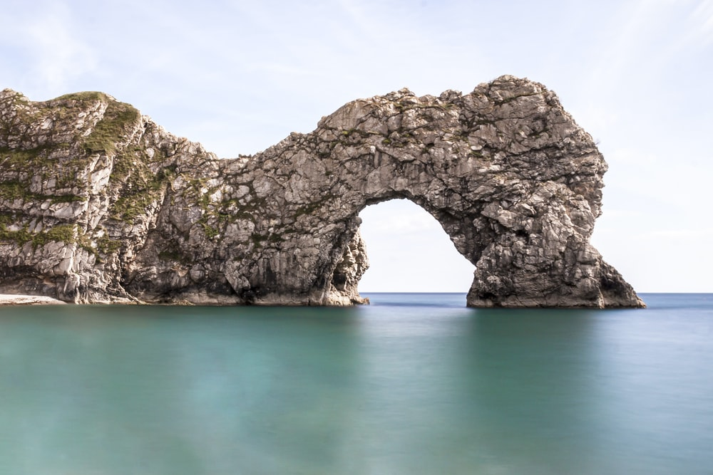 gray rock formation on blue sea under blue sky during daytime
